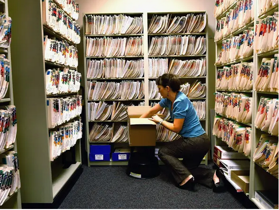 Keep copies of your health and medical records. Woman in office with hand in box dealing with records on top of black stool. Pretty girl with blue shirt black pants and black shoes.